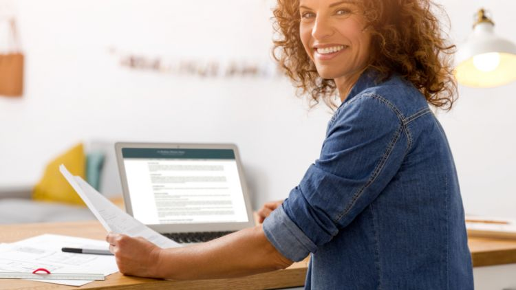 Middle-aged female entrepreneur who has returned to corporate America, smiling at the camera over her shoulder