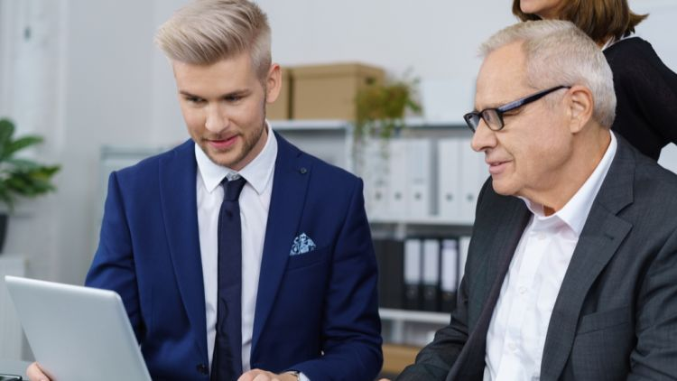 Young male manager showing something on his laptop to two older employees he manages