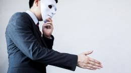 Image of a deceptive prospective employer holding a mask to his face while extending a hand for a handshake