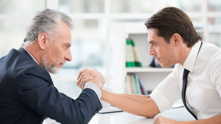 Younger and older male business men arm wrestle across a table in an office