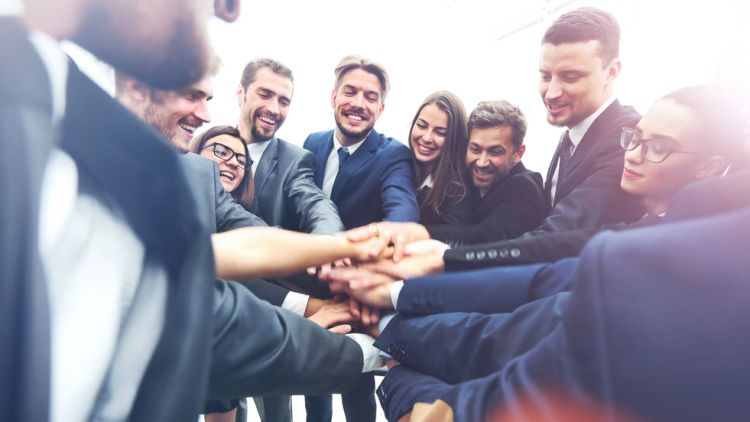 Diverse group of business people piling their hands in the center of a circle