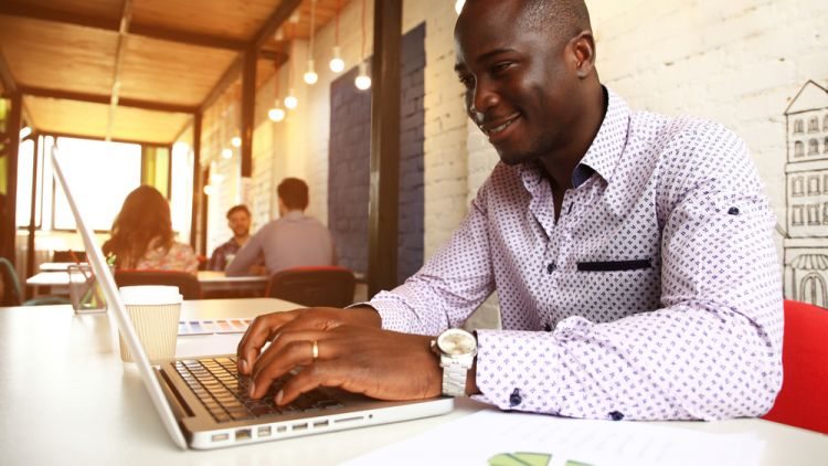 Young black, well-dressed man working on job application on his laptop in a trendy cafe