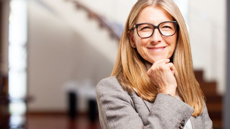 Middle-aged female executive smiling thoughtfully at the camera