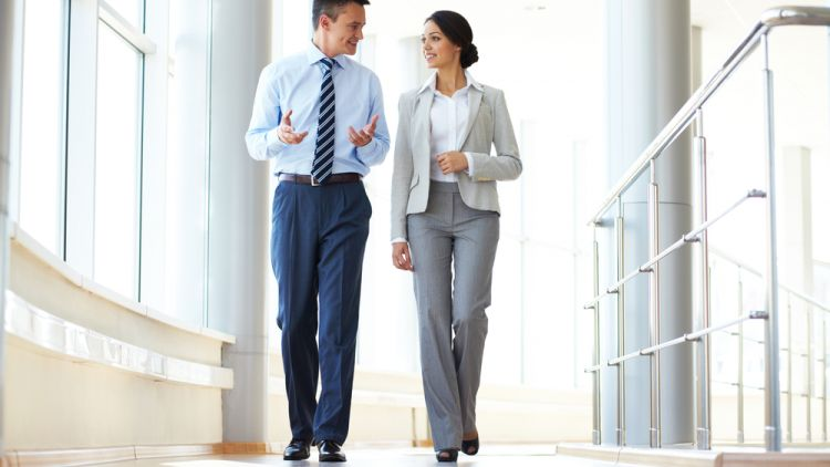 Business woman and man walking down the hall of a corporate office building and having a discussion
