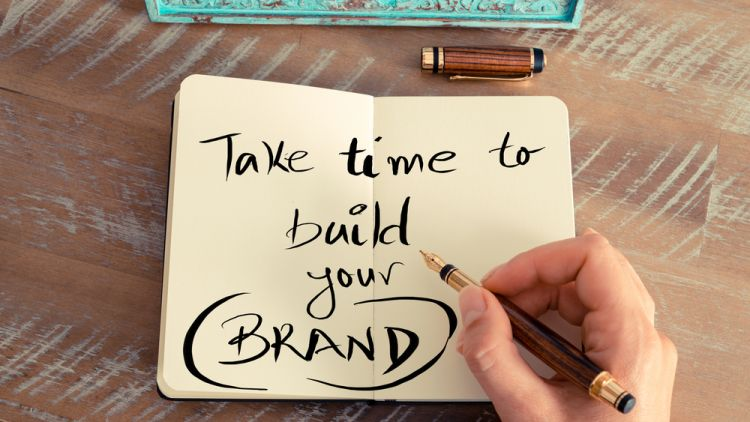 "Personal diary open on a table that reads, ""Take time to build your brand"" written in stylized writing by a hand holding a fountain pen"