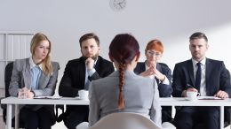 Four stern looking hiring managers face female interviewee