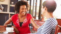 two women having a friendly conversation in a coffee shop