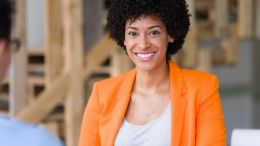 Smiling, young black business woman being interviewed