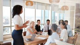 Black business woman, standing and delegating to her team in a conference room