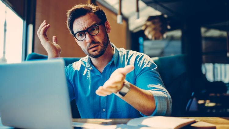 Man at computer struggling to record his thoughts in his resume. Throwing hands up in exasperation.