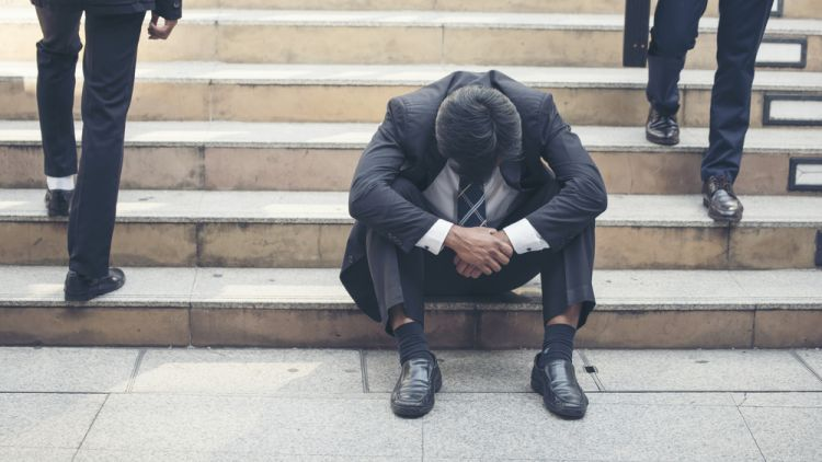 Man who lost his job sitting on office steps head and shoulders slumped as people pass him by