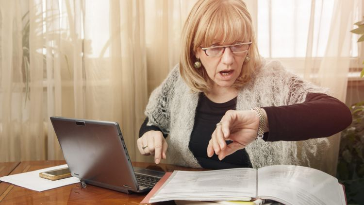 Middle-aged woman working in home office looking in surprise at her watch wondering where does the time go