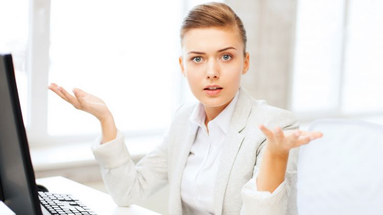 """Business woman sitting at desk with palms facing up asking, """"how what?"""""""