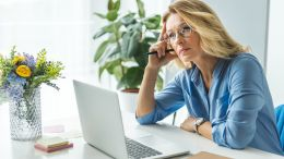 Executive businesswoman thinking at her desk looking at her laptop