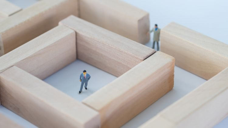 2 businessmen figurines in a maze made out of wooden blocks trying to work around their problems