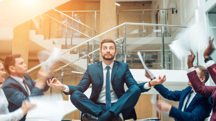 Businessman looking very zen while meditating on a conference table surrounded by colleagues throwing paper work at him. He is in an organization built on brain friendly values
