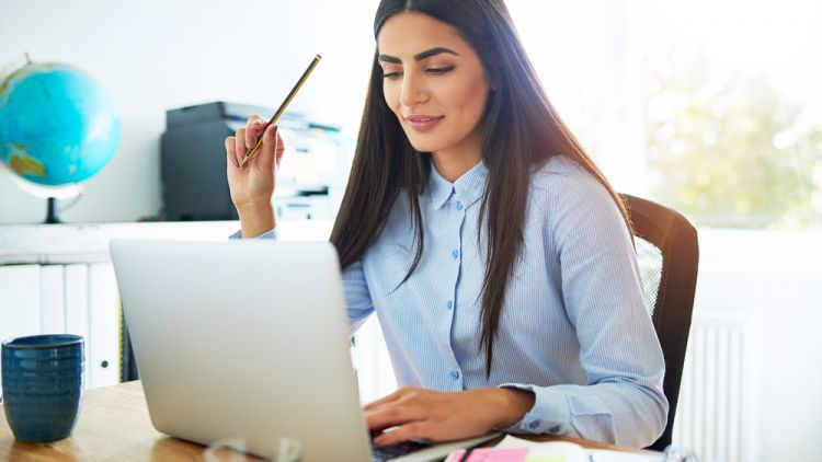 Business woman sitting at her desk thinking about smart strategies to get herself promoted