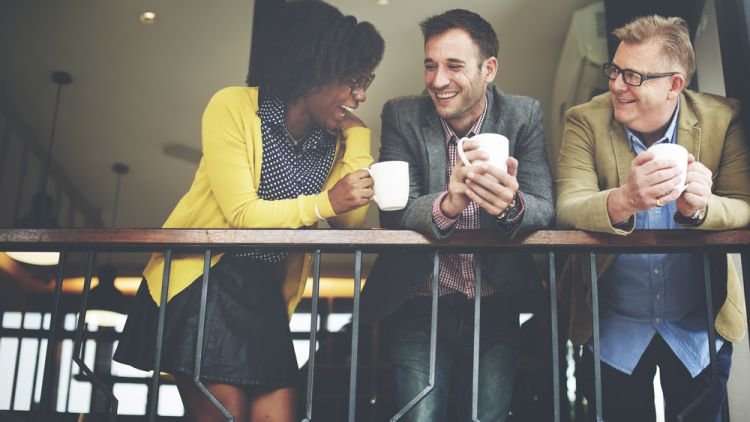 Diverse coworkers talk and network over coffee in their office