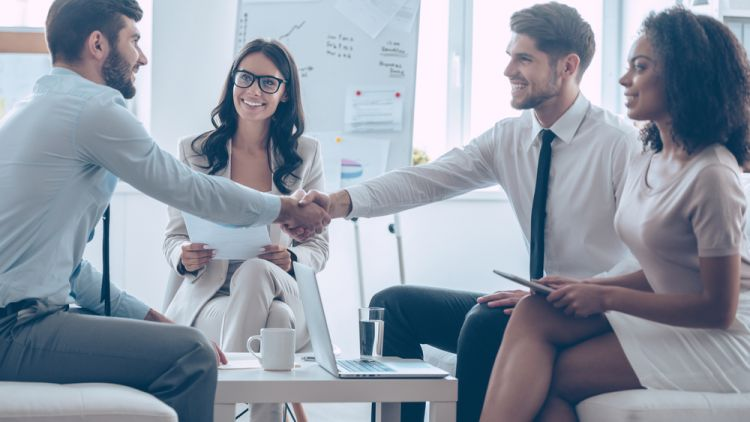 New employee shaking hands with coworkers on first day of new job