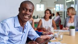 black business man, individual contributor, in meeting smiling at camera