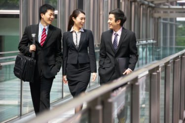 two businessmen and a business woman walk outside an office building, smiling