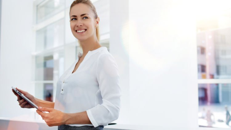 confident woman leader looks up and smiles while working on a tablet.