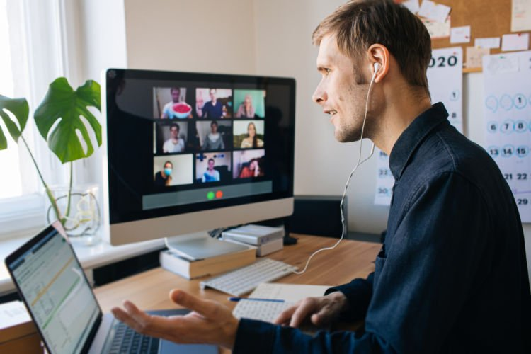 A newly hired business leader talks to his colleagues in a video conference