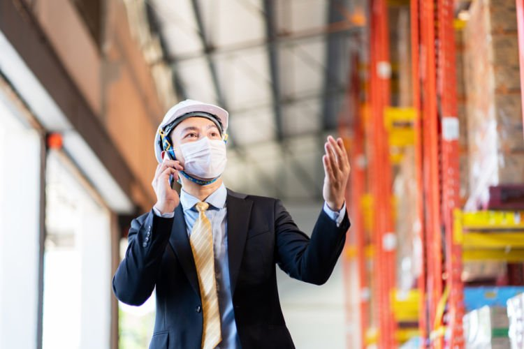 An executive tours his company's warehouse while wearing a mask to protect against COVID-19