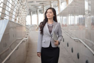 Executive in a skirt and blazer walks down a stairwell, looking in the distance